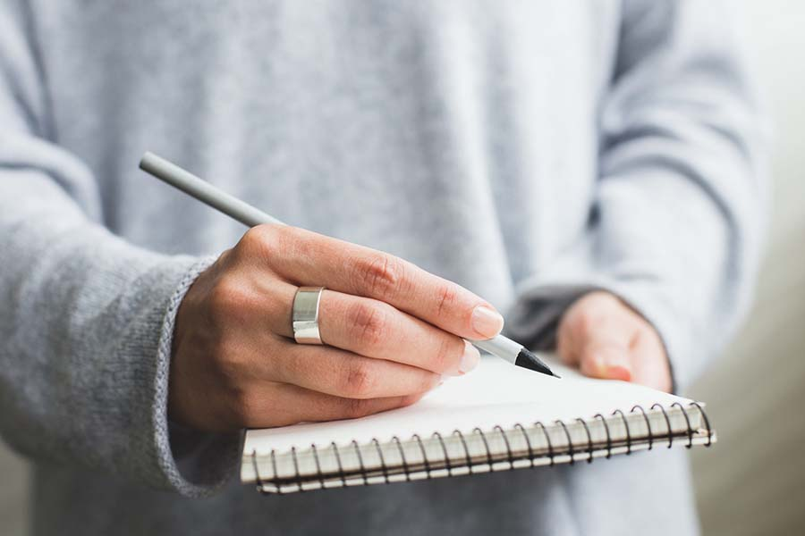 Person with a grey sweatshirt holding a grey pen and a white pad of paper ready to write information down