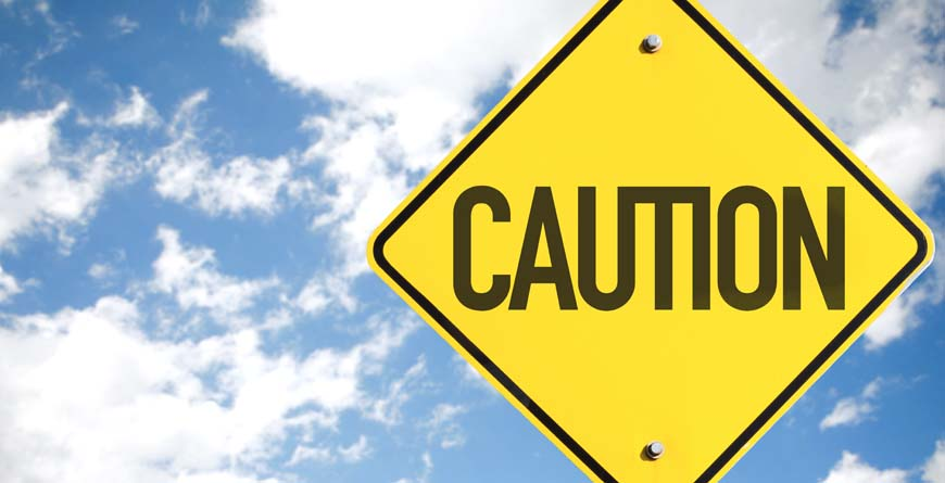 a yellow sign that says caution in black lettering with a blue shy and white clouds in the background