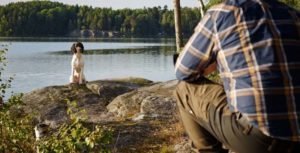 a white and black dog sitting on a rock facing a man from a distance wearing brown pants and a blue and brown plaid shirt next to a lake with green trees surrounding