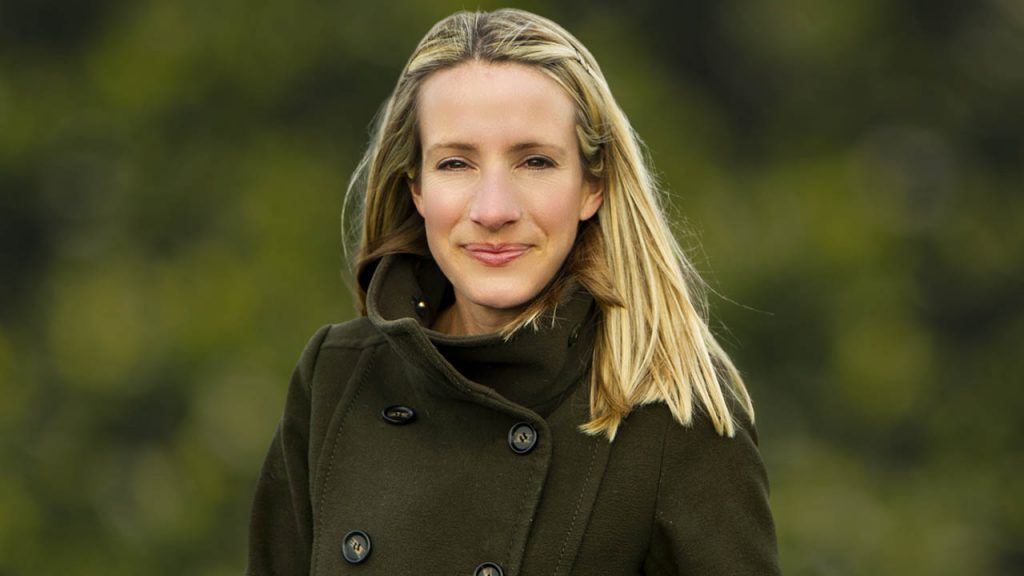 beautiful blonde haired woman wearing a green winter coat looking at the camera with an out of focus green background