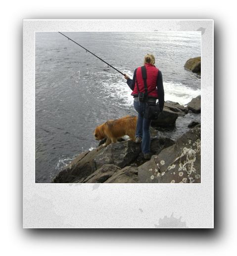 woman in a red puffy vest and blue jeans holding a long fishing pole and walking on rocks next to a brown haired dog next to the ocean water in Alaska