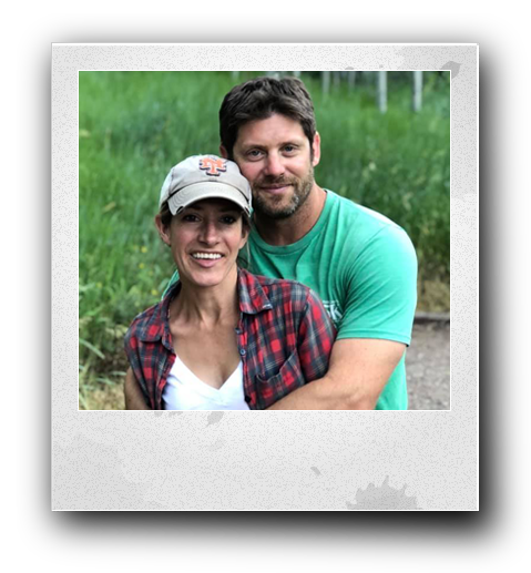 a man with a green shirt on is hugging a beautiful woman from behind who is wearing a new york mets hat with a plaid red shirt and white undershirt with green grass in the background in a poloroid frame