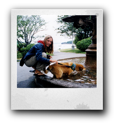 blonde hair woman with a blue coat and red hood and flip flops kneeling next to a park water fountain holding the leash of a brown dog who is in the water fountain drinking the water