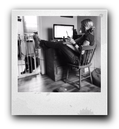 a black and white photo of Alyssa Rose sitting at a desktop computer with her legs kicked up and resting on the desk