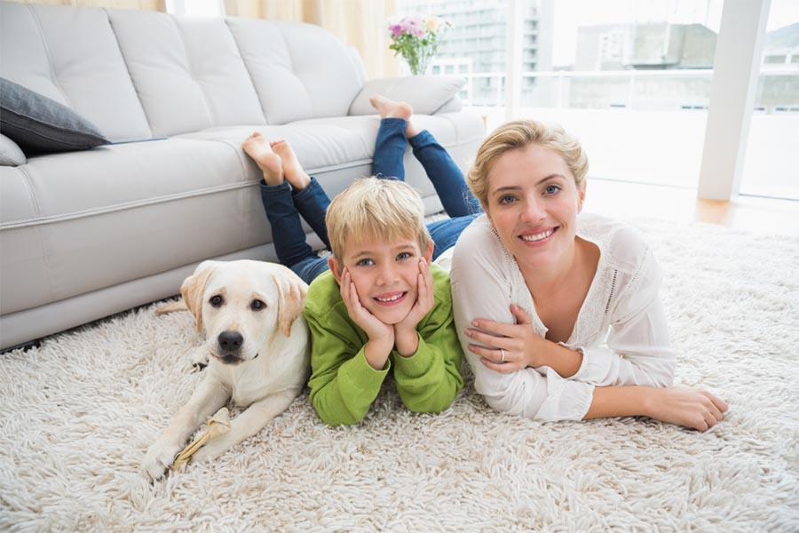 A woman in a white shirt laying on the living room white fluffy floor rug next to a boy with a green shirt and hands on face next to a white dog